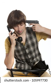 A young man with a handset and a pistol in his hand on a white background