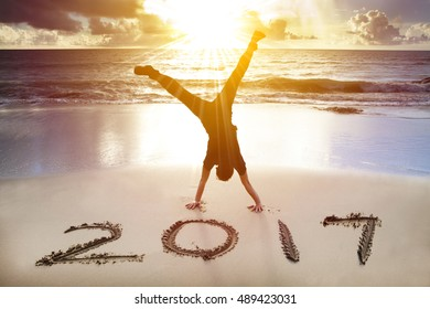 young man handstand on the beach.happy new year 2017 concept