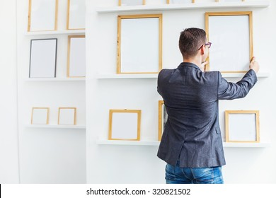 young man hanging a blank white frames in exhibition hall