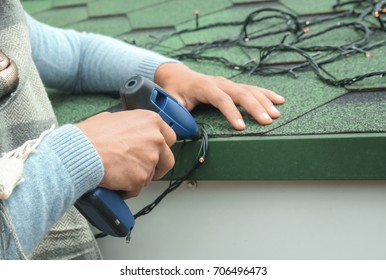Young man hanging Christmas lights on roof of house