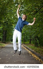 Young man hanging on a tree branch in a park alley - shallow DOF and little motion blur