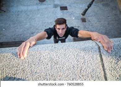 Young man hanging on wall on hands and trying to climb up while doing parkour.
