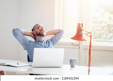 Young man happily laughing and resting at his office.