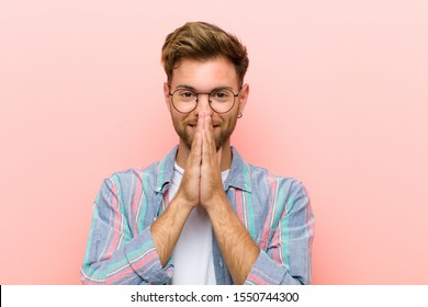 young man happy and excited, surprised and amazed covering mouth with hands, giggling with a cute expression against pink background