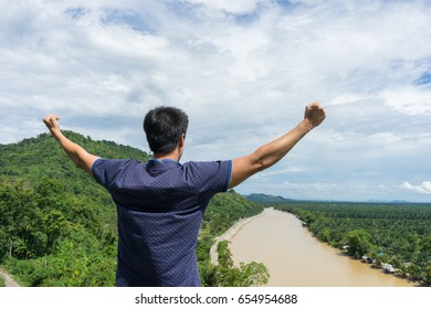 young man happy and show to strength with hands rise up on beautiful river Landscape with beautiful cloudy sky