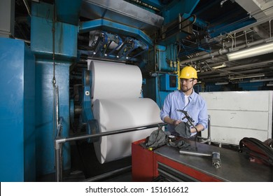 Young man in hardhat working in newspaper factory
