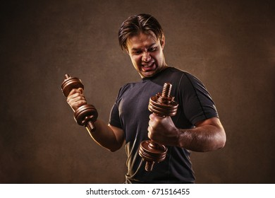Young man hardly doing exercises with dumbbells on stone wall background. Stress and effort emotions.