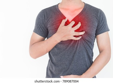Young man has chest pain, heart attack, hands pressing on chest.
