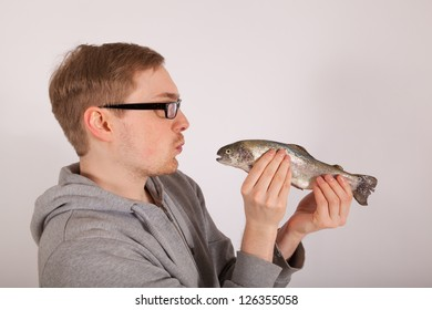 A young man has a fish in his hand