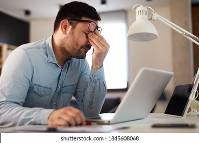 Young man has a headache at work while working on a laptop