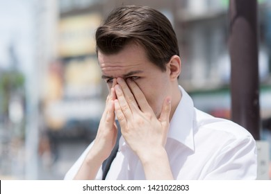 A young man has Itchy, watery, swollen eyes due to pollen allergy