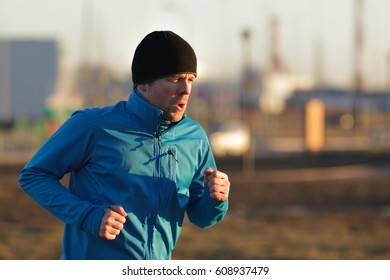 A young man in a hat and blue clothes runs in the morning on the background of factory pipes and smoke. To play sports in an urban environment