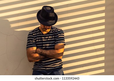 Young man with hat leaning against a wall with arms crossed