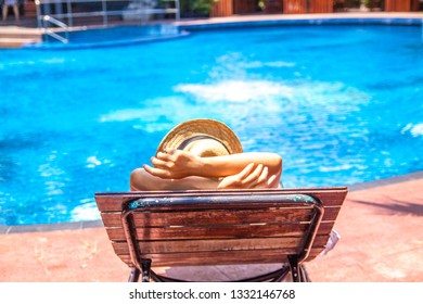 Young man in hat lies on louger near swimming pool for relax summer vacation concept.