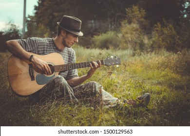 Young man in hat play on acoustic guitar sitting on the grass walley. Maybe blues man or country musician