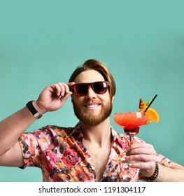 Young man in hat show thumb up drinking red margarita cocktail drink juice happy looking at camera over blue mint background