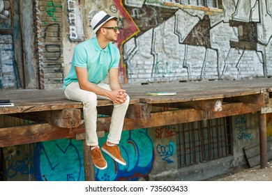 Young man with hat and sunglasses sitting outdoors