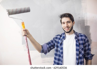 Young man have a fun and painting walls