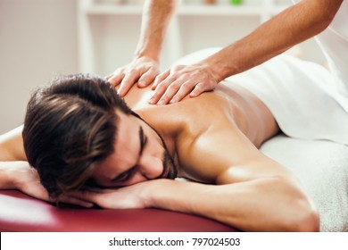 Young man is having back massage on spa treatment.