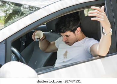 Young Man Having a Bad Day, Distracted Driver Looking Down in Frustration at Spilled Coffee on White T-Shirt While Sitting in Drivers Seat of Car