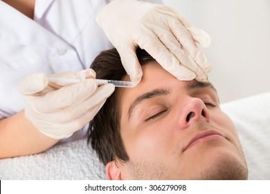 Young Man Having Botox Treatment At Beauty Clinic
