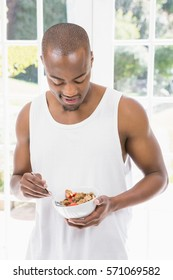 Young man having breakfast cereals at home