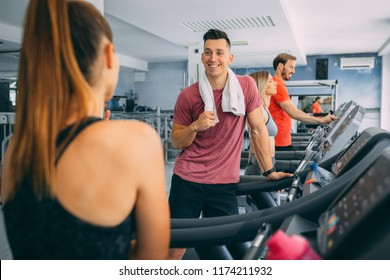 Young man having chat with frend after hardly training on treadmill machine in the gym.