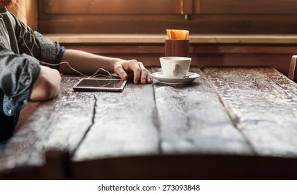Young man having a coffee break at the bar and listening to music with his tablet using earphones