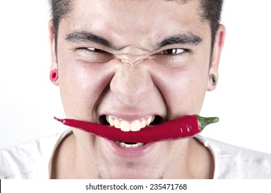 young man having fun, holding red hot chilly pepper in mouth.