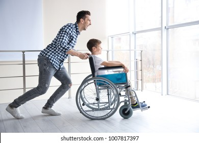 Young man having fun with little boy in wheelchair indoors