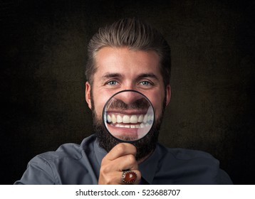 Young man having fun with magnifying glass