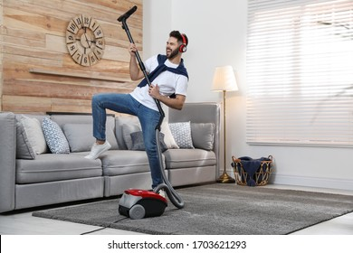 Young man having fun while vacuuming at home