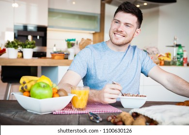 young man having a healthy breakfast in modern kitchen interior
