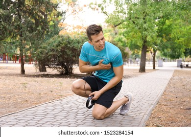 Young man having heart attack while running in park