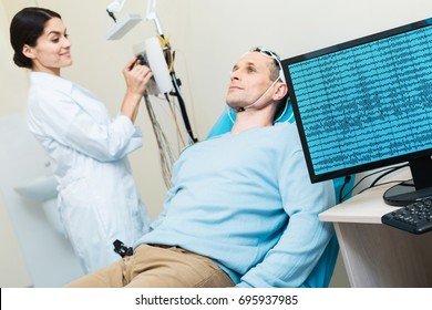 Young man having his brain waves recorded during electroencephalography