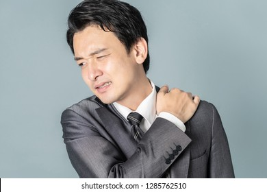 Young man having horribly stiff shoulders.