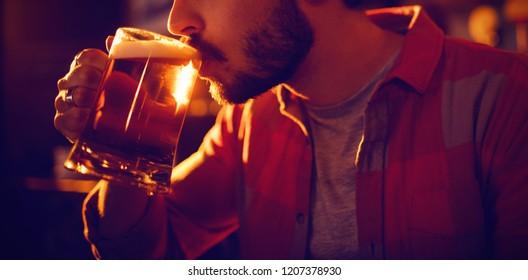 Young man having mug of beer in pub
