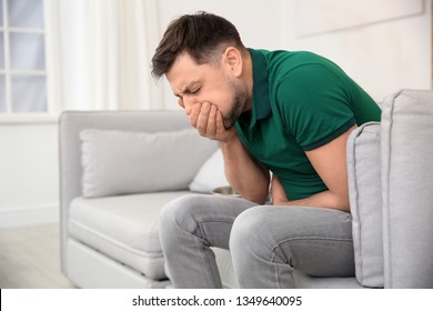 Young man having nausea at home. Space for text