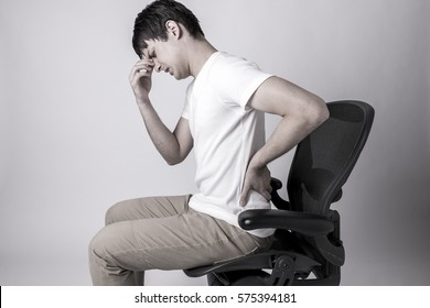 young man having a pain in his head and lower back