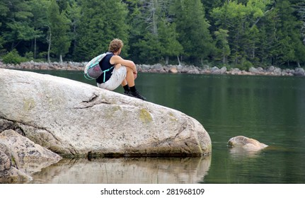 Young man having rest on the beautiful lake coast. Active life style concept