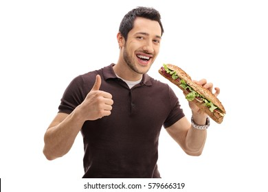 Young man having a sandwich and making a thumb up gesture isolated on white background