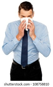Young man having severe cold. Sneezing and cleaning nose with tissue paper
