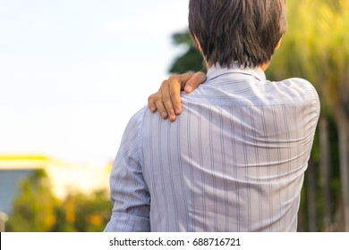 Young man having shoulder pain. Businessman has a shoulder pain.
