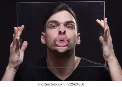 young man head face hard pressed against glass, hands holding it. making face, funny, bizarre, weird.