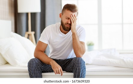 young  man with a headache, was sick in bed in the bedroom