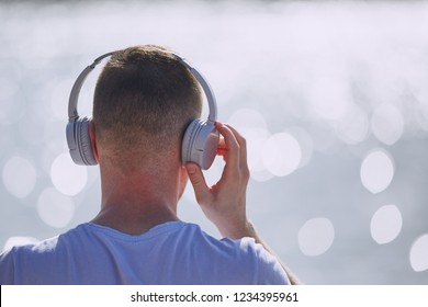Young man with headphones listening music against bokeh of waves of sea.