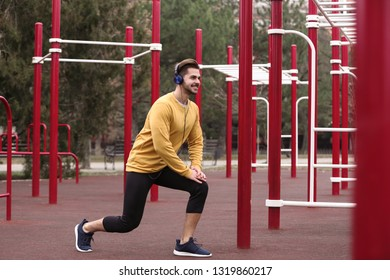 Young man with headphones listening to music and exercising on sports ground