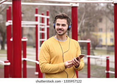 Young man with headphones listening to music on sports ground
