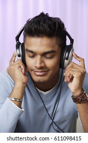 young man with headphones on, listening to music intently