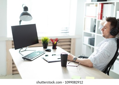 A young man in headphones sits at a computer desk.